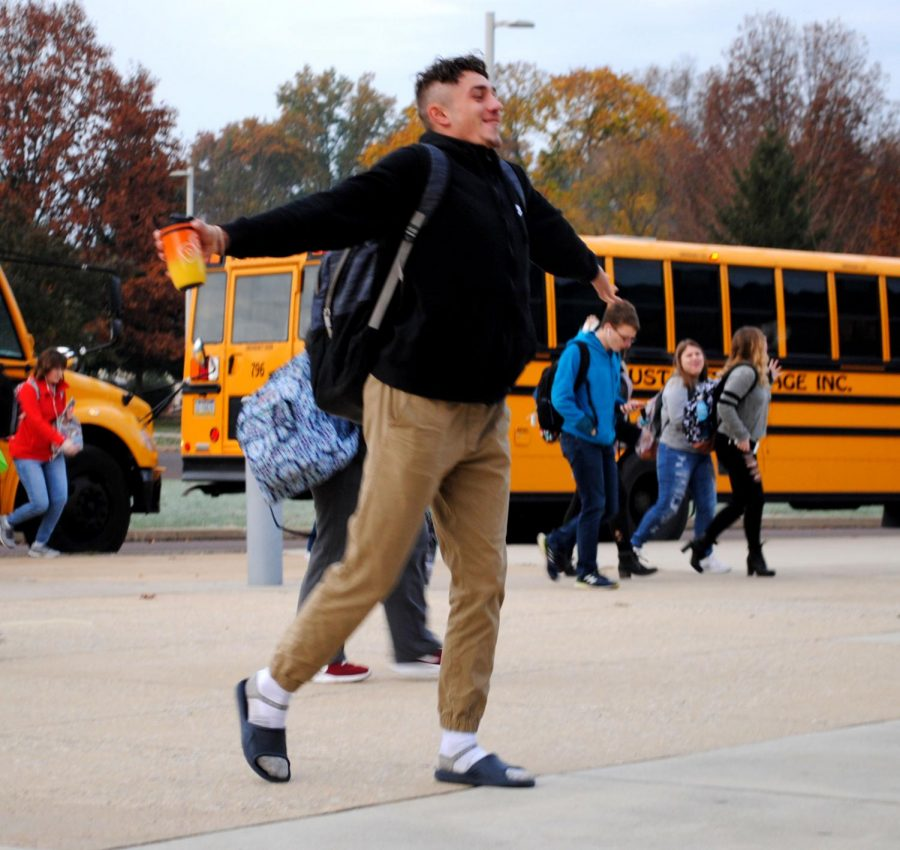 Spring-Ford student Max Raisner stretches as he walks into the building with classmates at 7:10 a.m. on  Monday, Nov. 12.