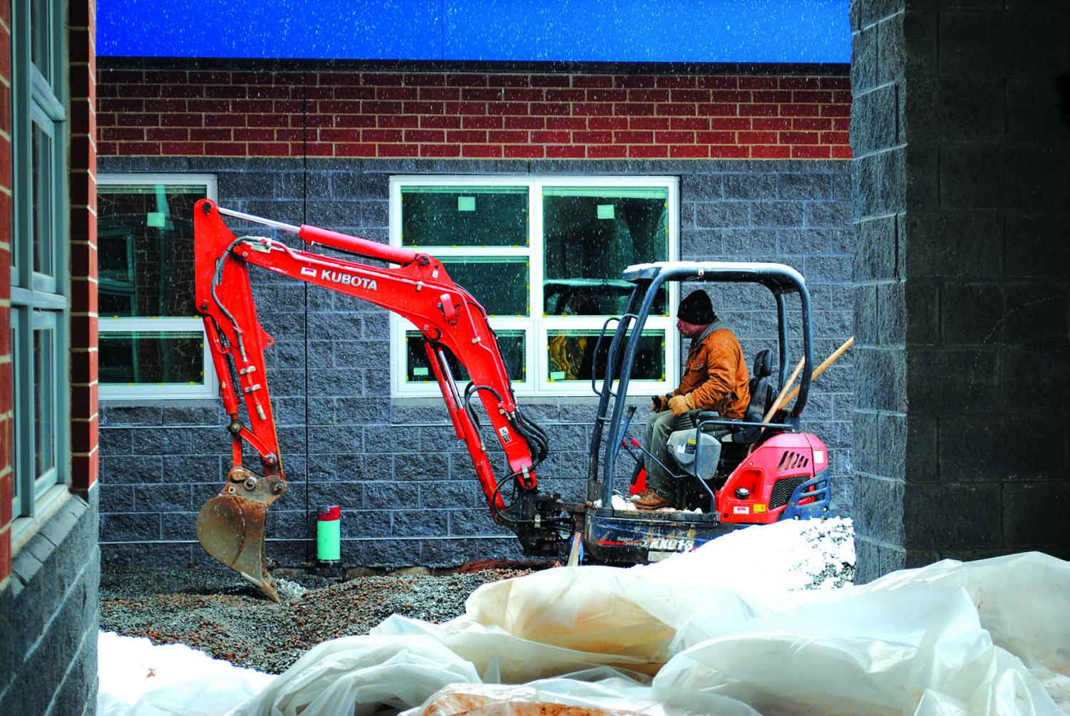 Construction+crews+work+on+the+addition+to+the+band+room+with+a+backhoe+during+a+snow+flurry+over+the+winter.+