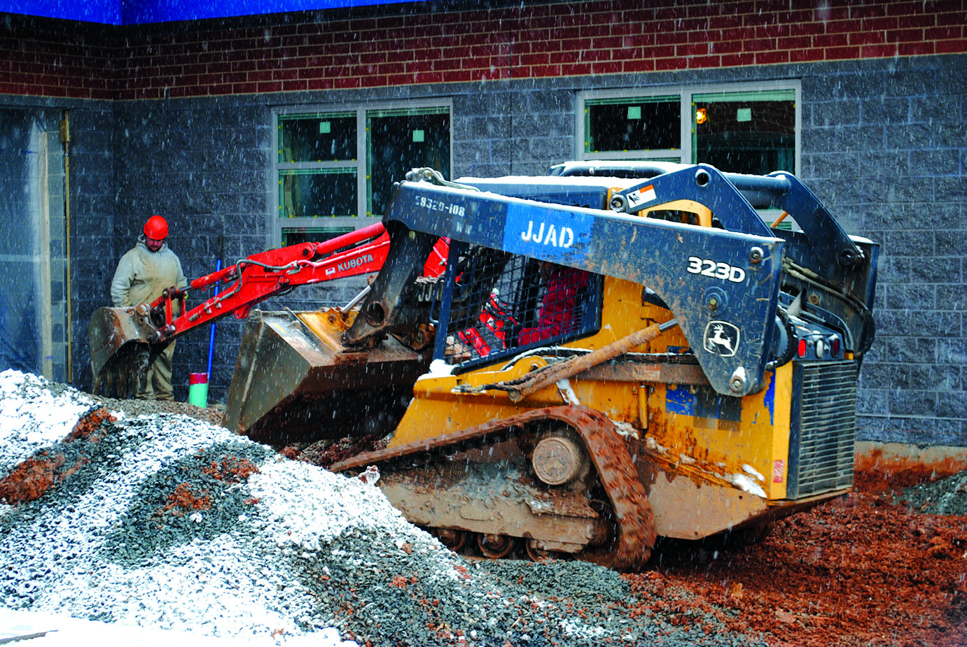Construction+crews+work+on+the+addition+to+the+band+room+with+a+bulldozer+and+backhoe+during+a+snow+flurry+over+the+winter.+