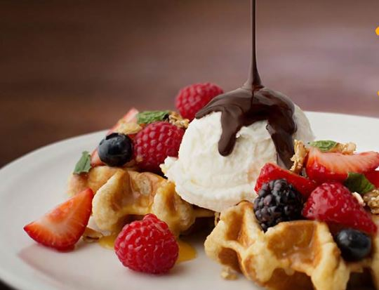 The Belgian waffles topped with ice cream, fruit, and chocolate is pictured from Max Brenner's menu.