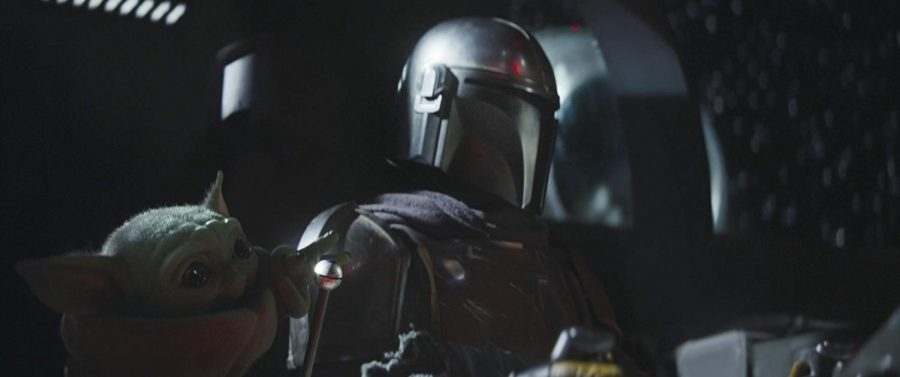 """The Mandalorian and """"The Child,"""" who resembles fan favorite Yoda, are pictured in the Disney + Star Wars spin-off """"The Mandalorian."""""""