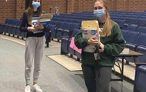Spring-Ford students Nadine Reid (left) and senior Noelle Reid pick up books on Sept. 16 in the high school auditorium. Students have had to adjust to remote learning this semester due to Covid-19 restrictions.