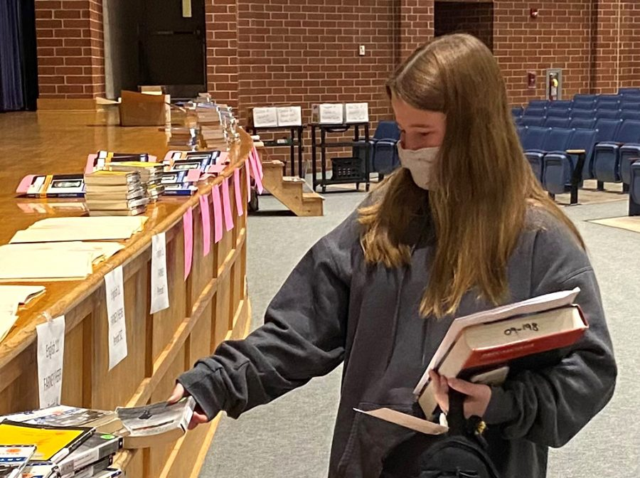 Spring-Ford senior Audrey Williams picks up material during book distribution earlier this fall.